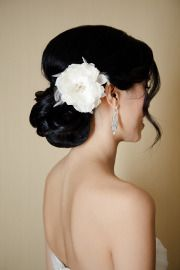 Low chignon with flower/feather hairpin.