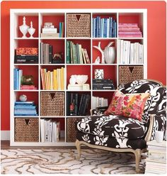 Inside this IKEA Expedit, the books are grouped by color, and also displayed both horizontally and vertically.  Practical baskets mix with glass bowls, vases and collectibles to form an aesthetically pleasing display on a brightly painted wall. Love the chair!  #CentsationalGirl