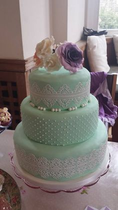 Mint Green and White wedding cake with sugar flowers in purple, white and peach.