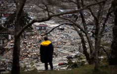 A man watches aftermath of Japanese tsunami 2011.