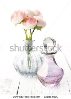 Perfume bottles with flowers on white wooden background by Gyorgy Barna, via Shutterstock