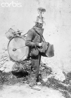Taormina, Sicily: Photo shows an Itinerant musician in the streets of Taormina in the island of Sicily who carries his various musical instruments on the top of his head, on his back, and in his hands. He operates the instruments at one time by moving alternately, his head, his feet and his hands. A most complete one man jazz band, 25 novembre 1925 - © Bettmann/CORBIS #lsicilia #sicily #taormina