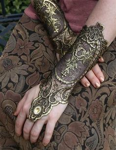 Exotic gloves spun from metallic thread peek adventurously from sleeves or lend exotic flair to bare arms.