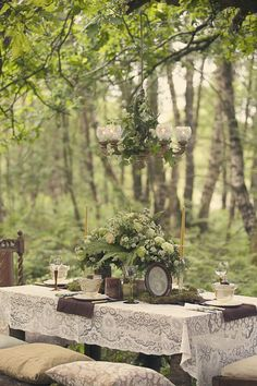 woodland retreat.  Green and white table.  Love the lace and chandelier.