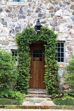 A stone pathway leads to the climbing vine-adorned side door, frequently used by the family.