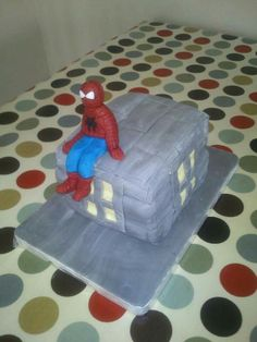 The cake. Sugar paste Spiderman sitting on top of a cake building.