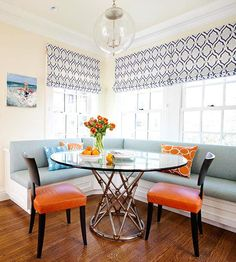 Fiery orange chairs and bold patterned pillows give this space a vibrant feel. More dining room decorating: http://www.bhg.com/rooms/dining-room/themes/sleek-modern-dining-rooms/?socsrc=bhgpin091813orangechairs