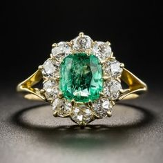 A bright light green old mine Colombian emerald, weighing one carat, glistens and glows from within a bright-white and sparkling halo composed of 10 old mine-cut diamonds in this late-Victorian classic, hand fabricated 18K yellow gold, dating from turn-of-the-last-century. 1/2 inch, currently ring size 5 1/2.