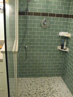 Love the green subway tile and the pebble floor