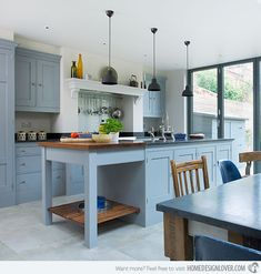Blue kitchen, butcher block table connected to stone topped island......traditional kitchen, brass hardware