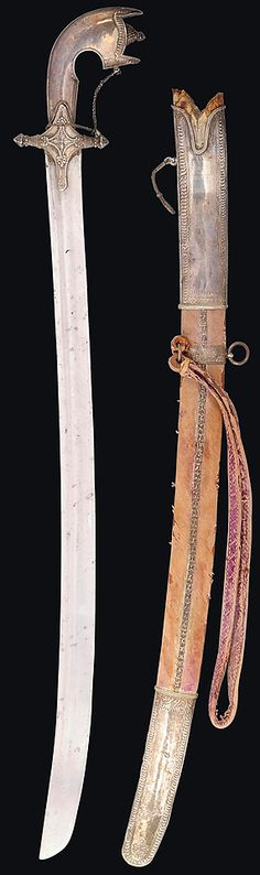 North African nimcha, 19th century,  sabre blade and pistol-shaped hilt with silver repoussé decoration, the scabbard with silver mounts engraved with arabesques and purple velvet cover (worn), with suspension loop and sword knop, 35in. (89cm.) .