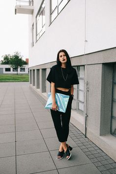 Elisa from www.schwarzersamt.com is wearing a all black look with blue details. She is wearing a black crop top from black blessed via The Backyard, loose fit H&M pants, Miista shoes, and a blue THE RAGGED PRIEST clutch. It was shoot at the Bauhaus Building in Dessau