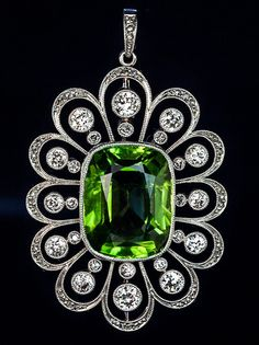 Art Deco Russian 13 Carat Peridot Diamond Platinum Pendant. St. Petersburg, circa 1930  The pendant is designed as an openwork flower head, crafted in platinum and 14K gold, centered with a large cushion cut sparkling lime green peridot, called chrysolite (golden stone) in Russia.  Peridots / chrysolites of this size and clarity are rare.   The stone... estimated weight 13.07 ct.  The stylized milgrain petals are set with old European and rose cut diamonds 2.30 ctw