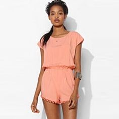 """Staring At Stars Peach Tie Back Romper NWOT Peach colored romper with short sleeves and short shorts lined with Pom poms. Slight open back with tie closure. Never been worn but I took the tags off. Model is 5'10"""". Measurements taken laying flat: bust- 18""""; waist- 11.5""""(elastic); length- 28"""" Staring at Stars Other"""