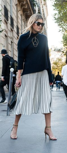 A pleated skirt and a classic black sweater with a statement necklace
