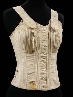 1890 Girl's 'Jaeger' corset. Made of unbleached cream wool, with a woollen braid lace passing through nickel eyelets and at the front with mother-of-pearl buttons attached to very long cotton threads. There are two pearl buttons stitched at each side seam, presumably for the suspenders. The V&A, London.