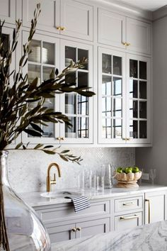 Lovely butler pantry with grey cabinets and gold hardware.