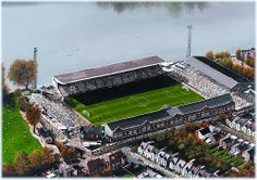 Famous old painting showing a supporter's standside view of Craven Cottage, home of Fulham Football Club (1896 to present); currently in the English Premiership. Location; Fulham, London; ground capacity: 26,300. If you would like to buy the original artwork of this image, please contact us.