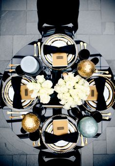 We love this dramatic black and gold table-scape, complete with a black bow-shaped napkin on each plate. See more photos from Style Me Pretty Great Gatsby Themed Party, Gatsby Party, Great Gatsby Wedding, Gold Wedding Decorations, Decor Wedding, Centrepiece Wedding, Masquerade Decorations, Dinner Party Decorations, Dinner Parties