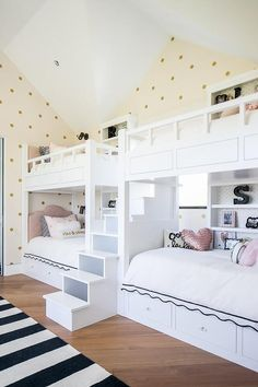 Under a vaulted ceiling, gold dots wallpaper covers the walls of a stylish girls' bunk room furnished with white bunk beds separated by white stairs.