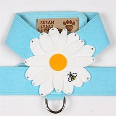 This blue dog walking harness is blooming with beauty! The unique floral dog harness designed by Susan Lanci features a large daisy flower with dimensional petals each accented with a sparkling Swarovski crystal. An embroidered bumble bee buzzes at the e