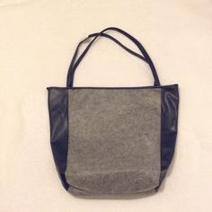 NWT Pleather and felt tote bag Gray and navy tote. Gray area is felt with a wool-like feel and navy is pleather. Nylon navy blue lining inside. Drop handle: 10 inches. Length: 17 inches. Width: 19 inches. Lightweight and holds all of your essentials! Faint white marking on bag, as seen in 2nd photo. MAKE ME AN OFFER❗️❗️❗️ Feel free to ask me any questions Bags Totes