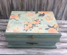 Paris themed jewelry box in Pale Blue and Pink, with accents in light Peach and Green  Vintage jewelry box has been painted and given a complete face lift with the allure of Shabby Chic Paris! ~~~ Beautiful. The top features lovely antiqued roses and butterflies... And Fluer De Paris in scrolled lettering.  This jewelry box also has exellent storage. Open it up to reveal a mirror, necklace/bracelet hooks, ring pillow, earing compartment, and 4 small square compartments. The Lower drawer ...
