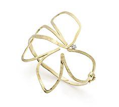 Pulseira de ouro amarelo 18K com diamante - Coleção Oscar Niemeyer Os desenhos livres, leves e cheios de curvas do famoso arquiteto Oscar Niemeyer inspiraram uma coleção de joias que leva a sua assinatura, criada em sua homenagem e a partir de seus próprios croquis. A obra de Niemeyer inclui também rabiscos de singela beleza, como aquele em que uma mão anônima segura uma flor de quatro folhas. Uma única linha dá forma à imagem, que remete aos desenhos infantis, tamanha é sua simplicidade…