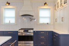 Wakefield - Kraftmaid cabinetry in blue with white wall cabinets. Range wood hood to give a decorative accent