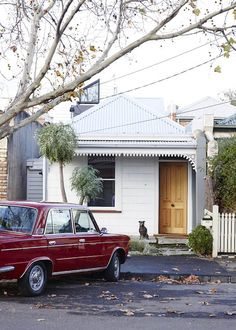 The renovated North Fitzroy cottage of Daniel Stray and Kc Reynolds. Facade of house with two of Daniel's favourite things, his vintage Fiat 125 and Poppy the Staffy! Photo – Sean Fennessy. Production – Lucy Feagins / The Design Files.