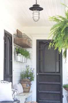#Farmhouse lighting, galvanized buckets, chickenwire cubby shelf with hooks, ferns, benches, old pickle jar for storing birdseed, all work together to create an inviting farmhouse back #porch.