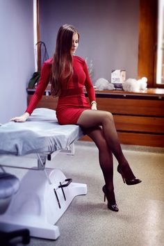 Ariadna sitting pretty on the bed in a red dress and black tights