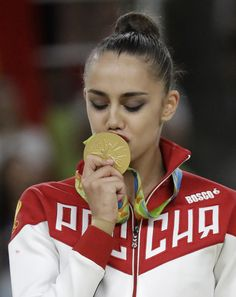 Russia's Margarita Mamun kisses her gold medal for rhythmic gymnastics individual all-around at the 2016 Summer Olympics in Rio de Janeiro, Brazil, Saturday,...