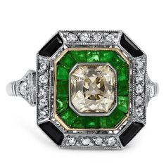 The Seville Ring from Brilliant Earth - This stately platinum Art Deco ring features an old mine cut cushion-shaped diamond surrounded by sixteen French cut natural emerald accents. The outer rim showcases twenty-six rose cut diamond accents and four French cut onyx accents for a regal effect (approx. 1.29 total carat weight).