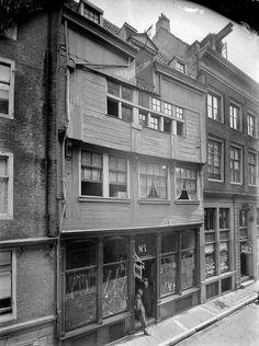 """Waarschijnlijk één van de oudste (bewaarde) houten huizen van Amsterdam: Zeedijk 1. Bijzonder verhaal: in dit pand was de herberg """"het Aepjen"""" gevestigd. Het was niet direct een 5-sterren hotel. Integendeel. Het was (op zijn Amsterdams gezegd) een kolerezooi. Volgens de overlevering was dit logement de basis van het spreekwoord """"in de aap gelogeerd""""... De foto is in 1915 gemaakt door C. Steenbergh"""