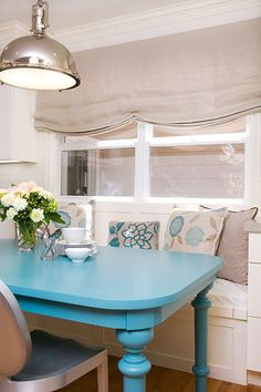 Gorgeous built-in breakfast nook with blue table and silver light fixture