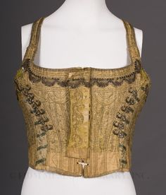 "Corselet: ca. 1790-1798, French, boning, embellishment of metallic elements (discs, galoon lace, hooks, embroidery). ""One source...described a decorative corset/corselet worn over a sleeveless dress with elbow length sleeves and decorated cuffs. The neckline was described as high and straight across the front...this decorative corset was once worn in regions of Southern France... but without an image it is impossible to document that [this item] is actually a bavarel."""
