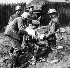German soldiers helping a wounded British prisoner. WW1 was the last conflict where sanitary ceasefires were respected. Stretcher bearers from all sides were able to work together in the no man's land.