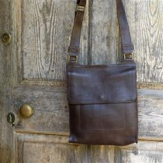 Messenger Leather Bag   This stylish messenger bag is hand made (fair trade) from a luxuriously thick dark chocolate brown leather. Each bag has been hand made by one craftsperson from start to finish with exceptional attention to detail. These beautiful bags are lined in dark brown cotton and contain a mobile phone and a zip pocket.  Size: 34cm x 28cm x 8cm (adjustable strap)  £124.95