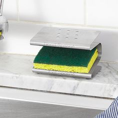 """Spongester This stainless steel rack helps expunge bacteria by keeping your """"good sponge"""" and """"evil sponge"""" separate."""