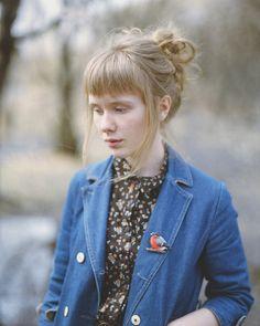 short full fringe, denim blazer, bird pin and floral shirt.