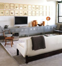 I'm on a storage solutions kick right now. 1) I like the metal cabinets lining the whole wall. 2) I like the grid-like row of pictures following the cabinet line. 3) I love white sofas.