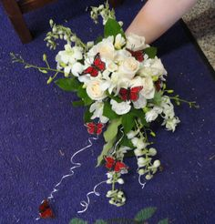 White cascading bouquet accented with red butterflies