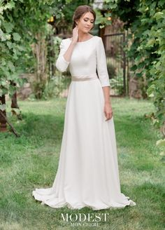 Style TR11971 from Mon Cheri Modest is classic simplicity at its best. This less-is-more slim A-line crepe modest wedding gown has three-quarter length sleeves with covered buttons, a flattering bateau neckline, a princess seamed bodice, a beaded natural waistline, a detachable satin ribbon at the waist, and a high back bodice with covered buttons down the zipper and onto the court train. Ivory dress includes a Champagne colored ribbon. White dress includes a White colored ribbon. Also…