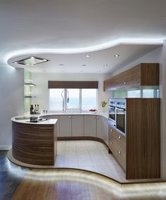 Contemporary Kitchen Design With Curve Wooden Kitchen Cabinet and White Countertop and Ceiling Lighting