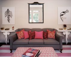 Living Room - A gray couch with pink pillows atop a striped rug - very cool tables and art work