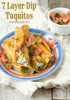 7 layer dip taquitos are stuffed with beans, sour cream, guacamole, and cheese and then fried to perfection and served with fresh pico.