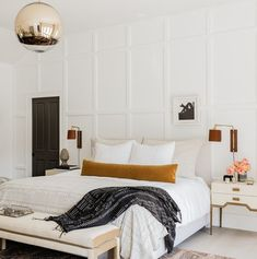 Custom millwork makes for a stately feature wall behind the headboard in the master bedroom. Dainty Art Deco-look nightstands with tapered legs add a shapely feminine appeal. See more — link in bio. Dream Bedroom, Home Decor Bedroom, Modern Bedroom, Master Bedroom, Trendy Bedroom, Design Bedroom, European Bedroom, Parisian Bedroom, Bedroom Ideas