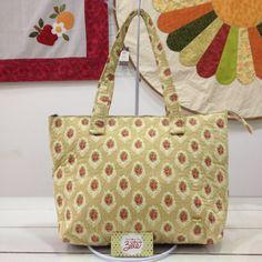 Bolsa produzida com tecido 100% algodão, com 3 divisórias, fechamento em zíper e quilt livre.