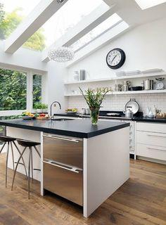 isla blanca con encimera negra en la cocina